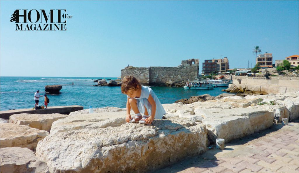 a young child with a blue dress bending on a big rock with the view of the sea around and many rocks and a castle in the sea