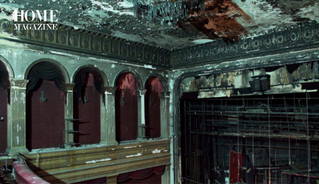 Damaged interior theater with grey walls and red furniture