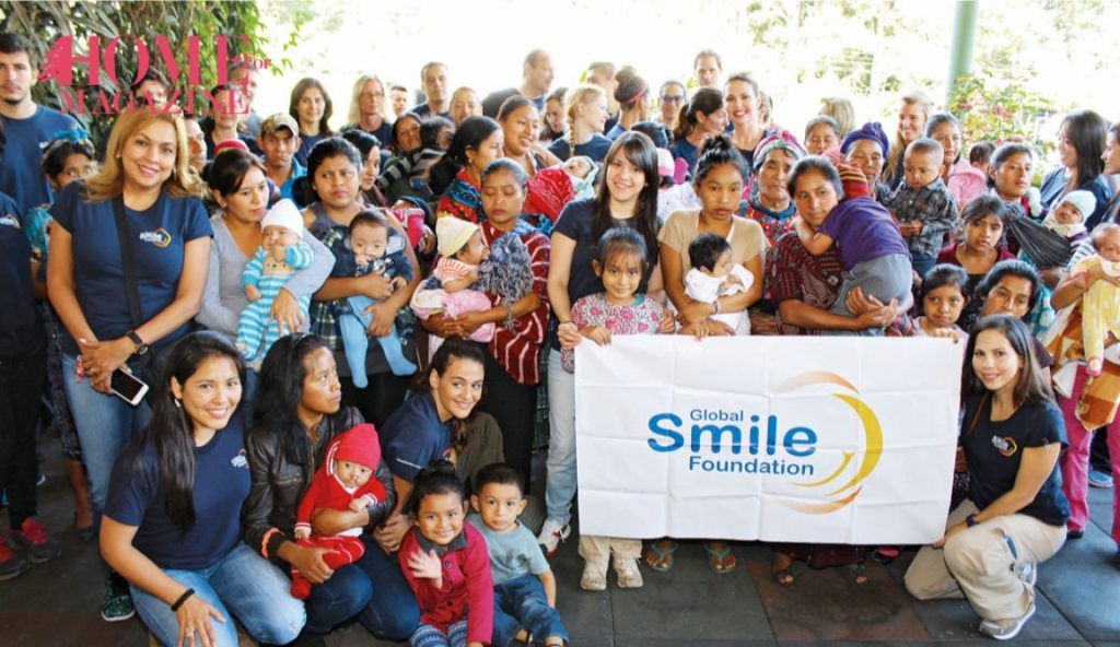 a group of people and kids holding a flag with Global smile foundation