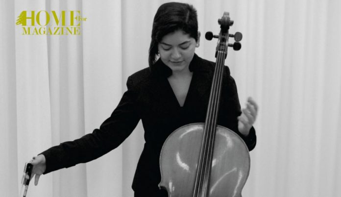 a girl wearing black with a cello in front of her with a hand towards it and the other a little far
