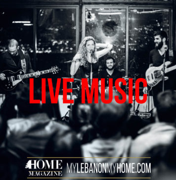 a band with 3 guys holding their guitars and a girl in the middle standing behind a microphone with her hand over her curly hair and the head of people looking at them