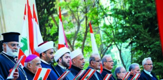 sheikh and priests standing next to each others while holding the a paper with ebanese flag and the lebanese flag all around