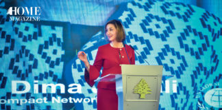 Woman speaker in red on stage with blue background