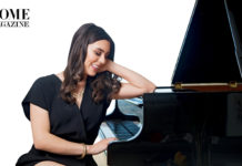 Woman in black smiling and laying arm on piano