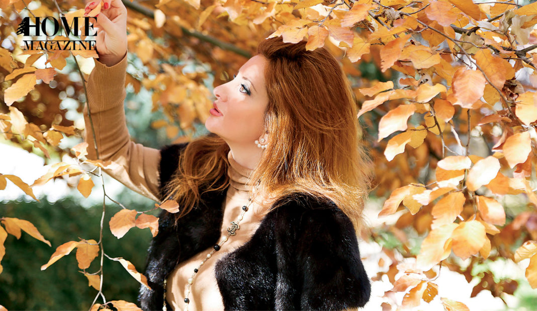 Woman in red hair holding brown leaf among trees
