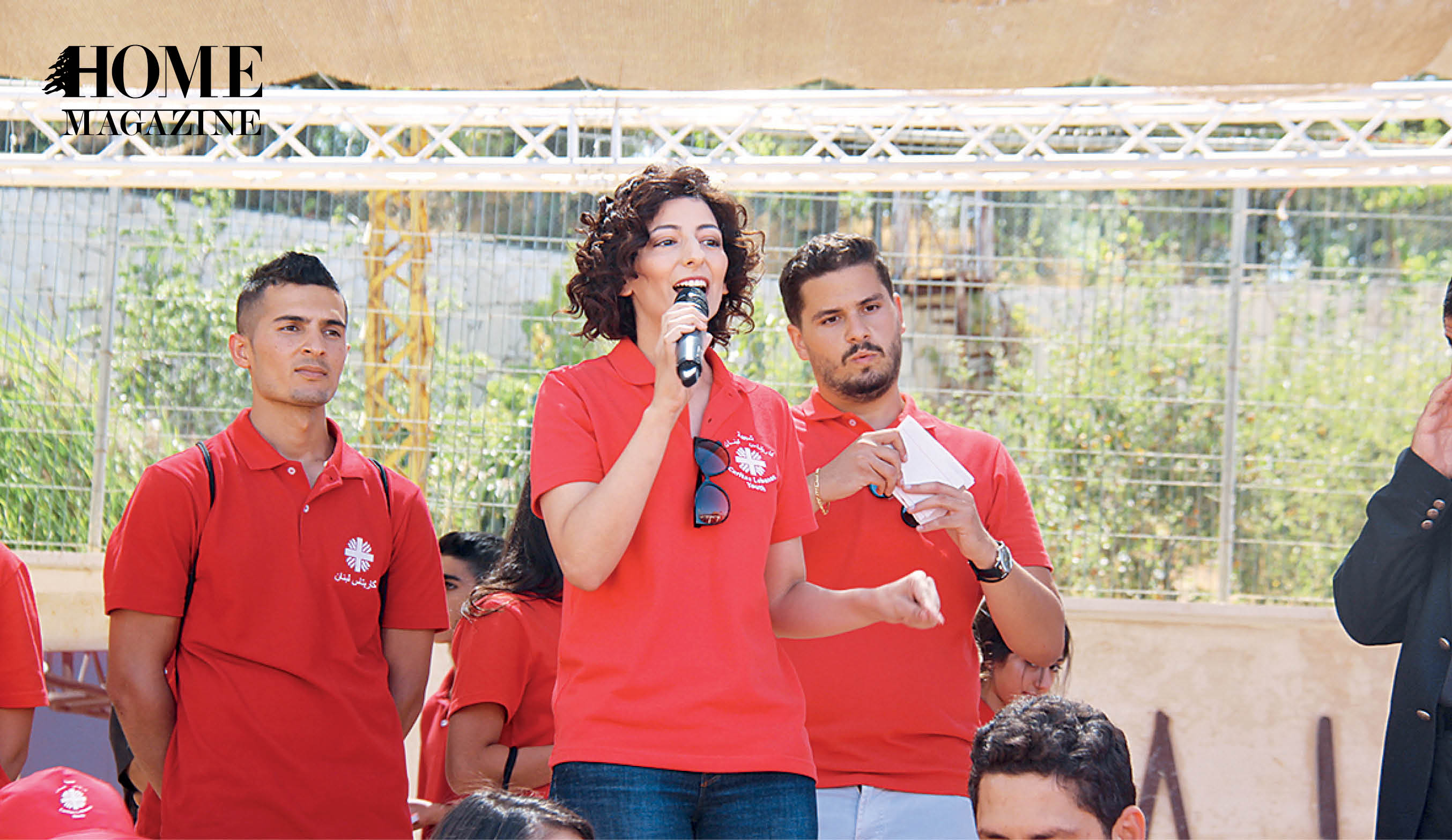 Woman in red tshirt speaking on microphone with two men in red tshirts behind