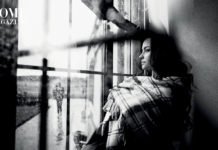 Girl with dark long hair and square-patterned blanket staring out of glass window