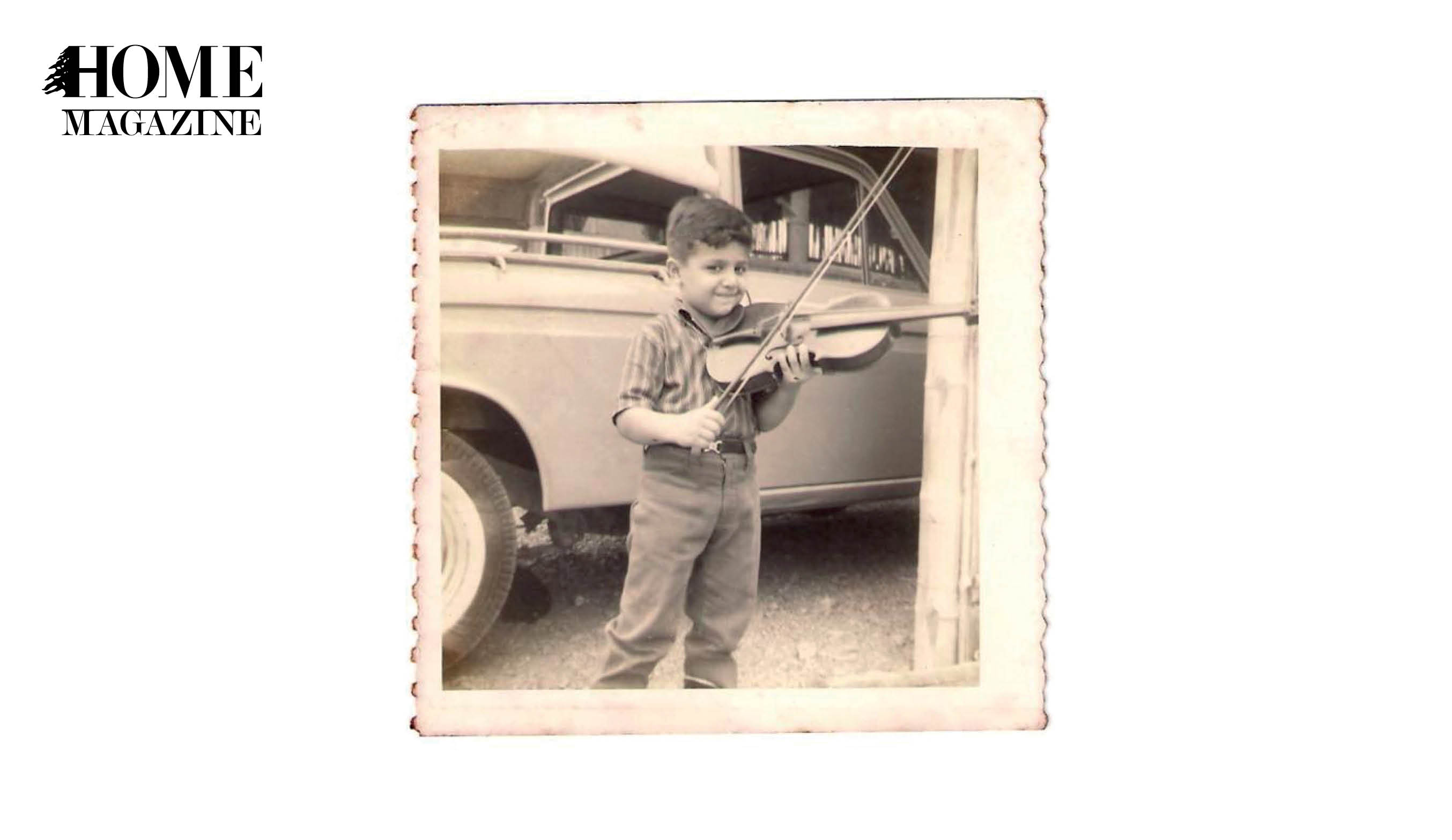 Litlle boy playing violin with a car in the background