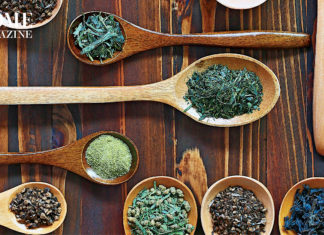 Green and black herbs in wood spoons