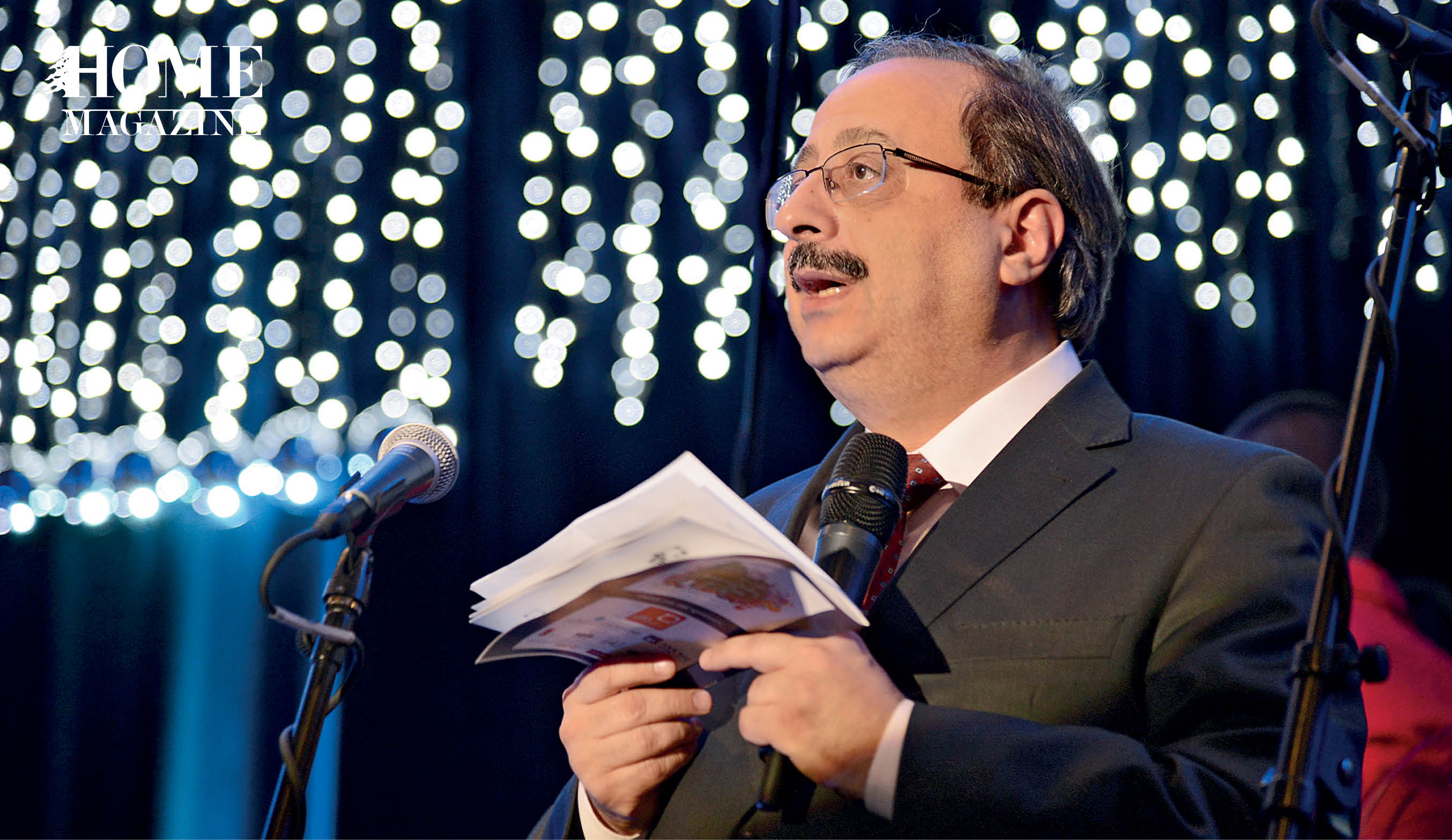 Bald man wearing eyeglasses speaking on a microphone with a notebook in his hands