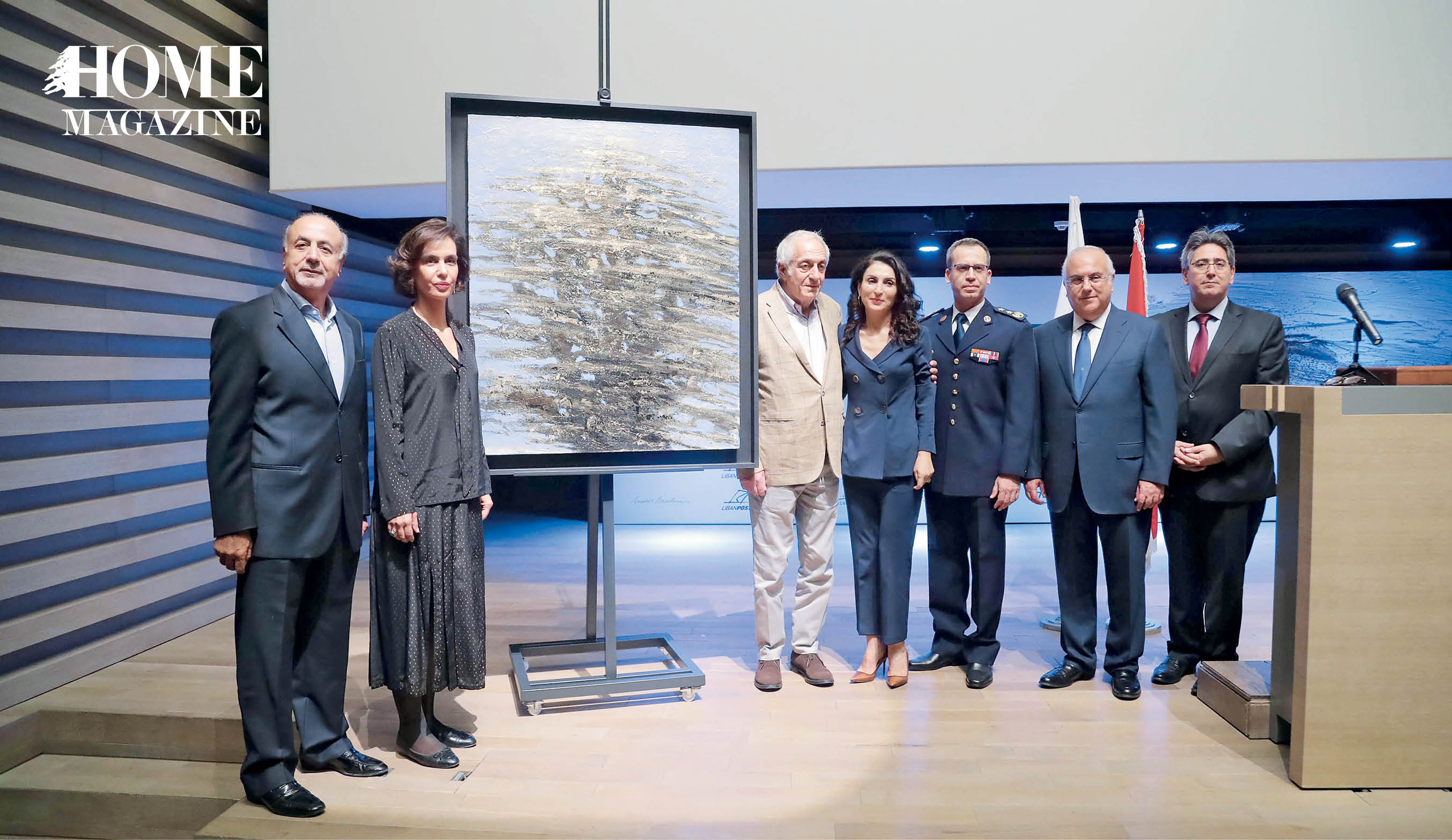 Men and women standing next to a painting