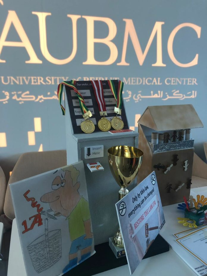 AUBMC logo with cards and medals