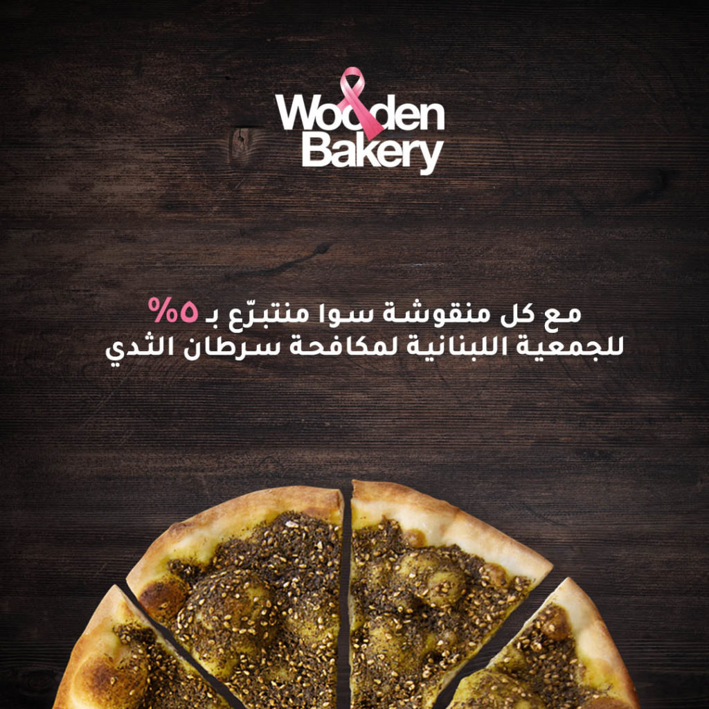 Mankoushe with thyme cut into 4 slices with words written in white and pink in arabic and english