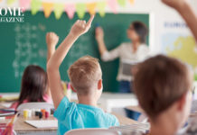 Kids raising hands in classroom with teacher in background