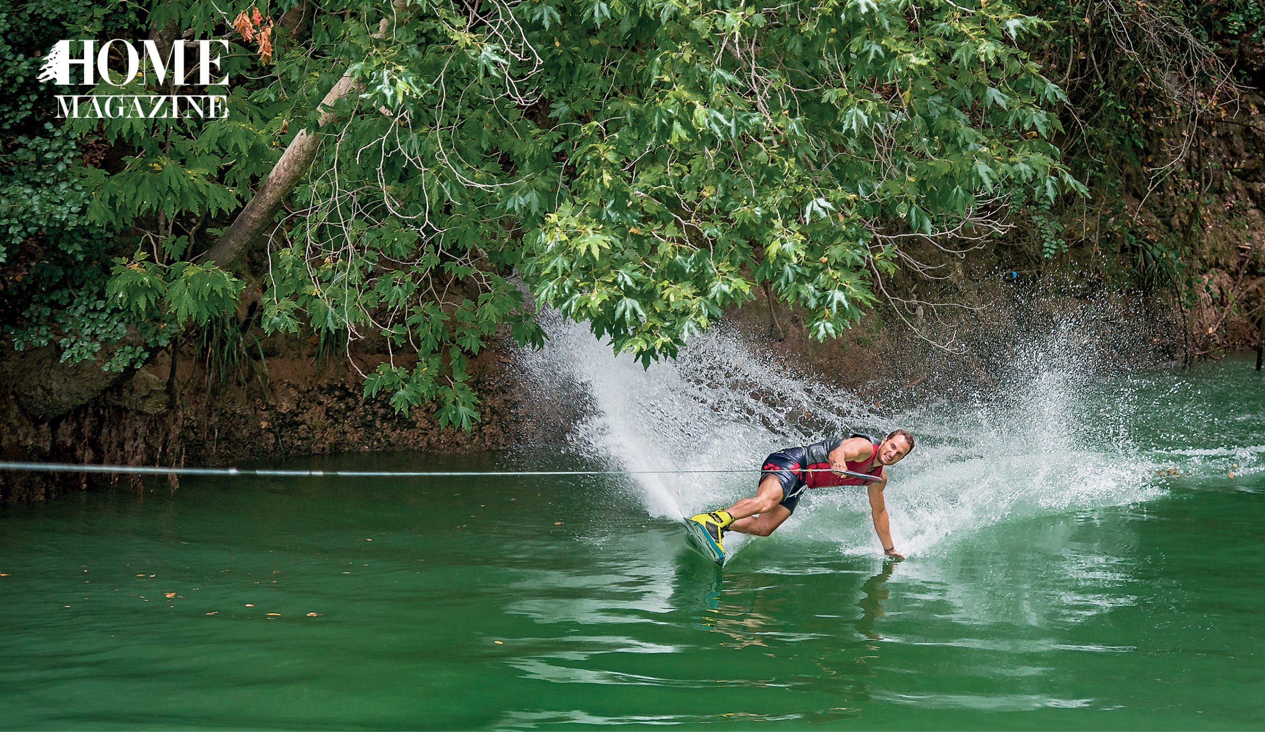 Man water surfing amidst green trees
