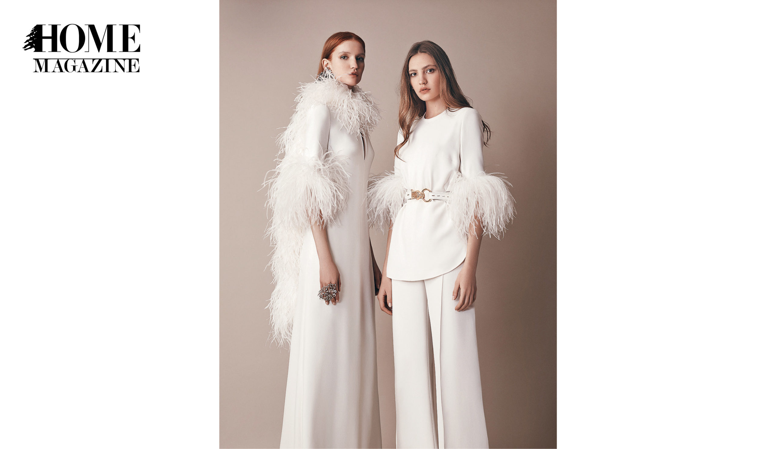 Two models wearing all white ensemble with feathers