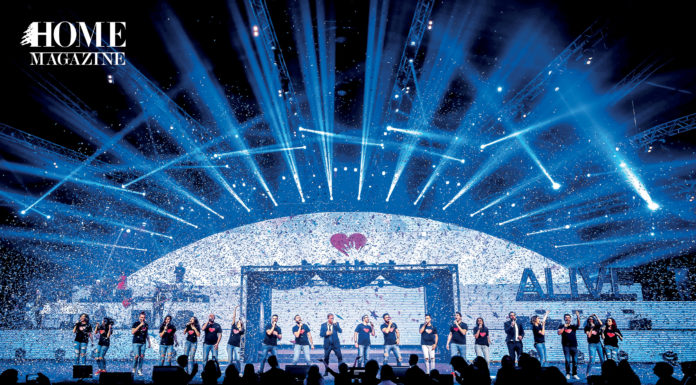 Group of people performing on a stage with blue lighting