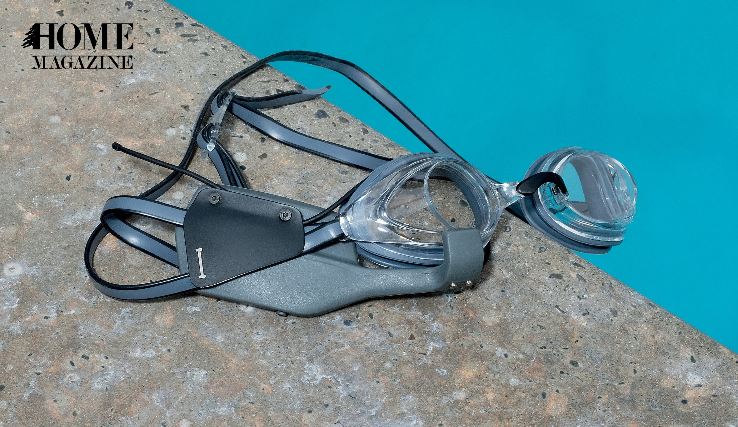 Grey swimming goggles of a pool's edge