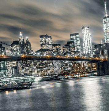 A bridge crossing waters amidst lightened buildings