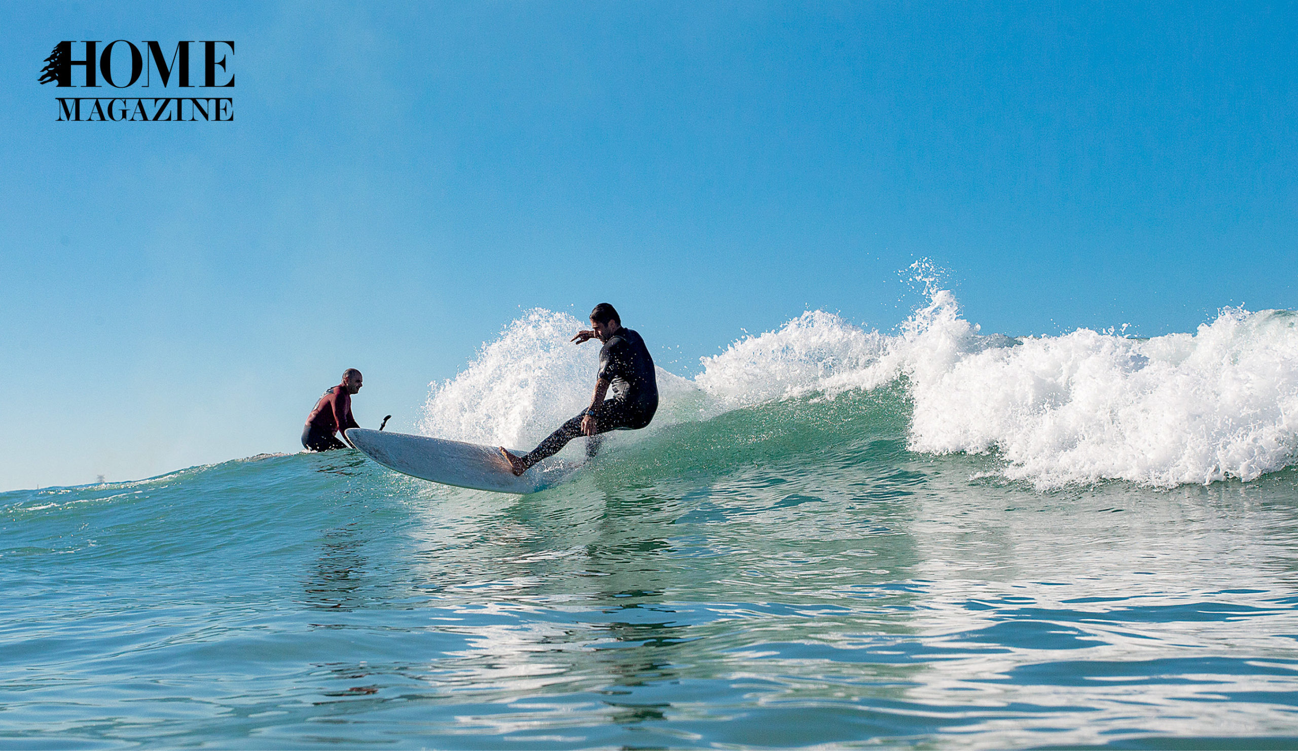 Two men riding waves of sea