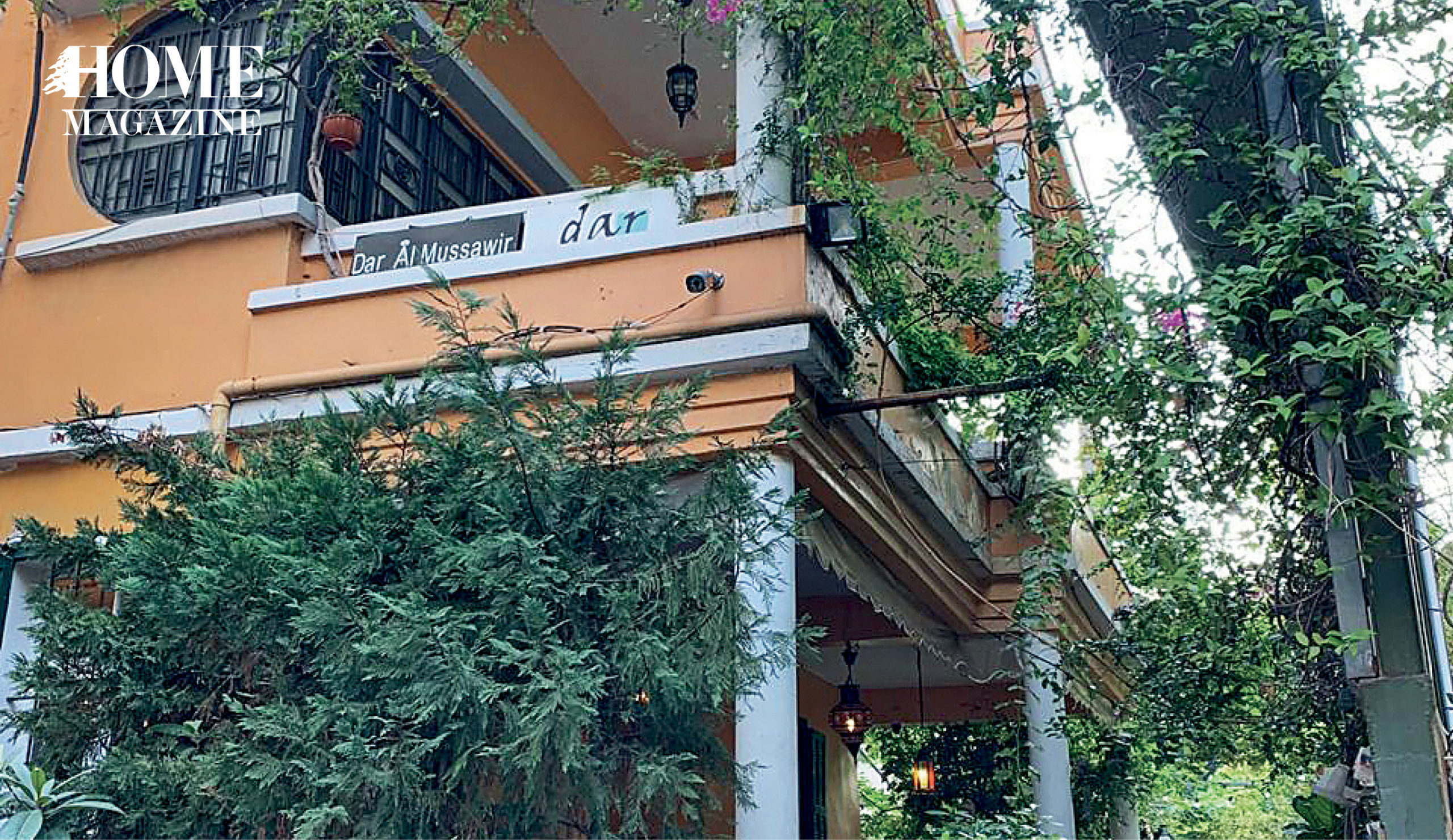 Orange painted building with green trees and plants