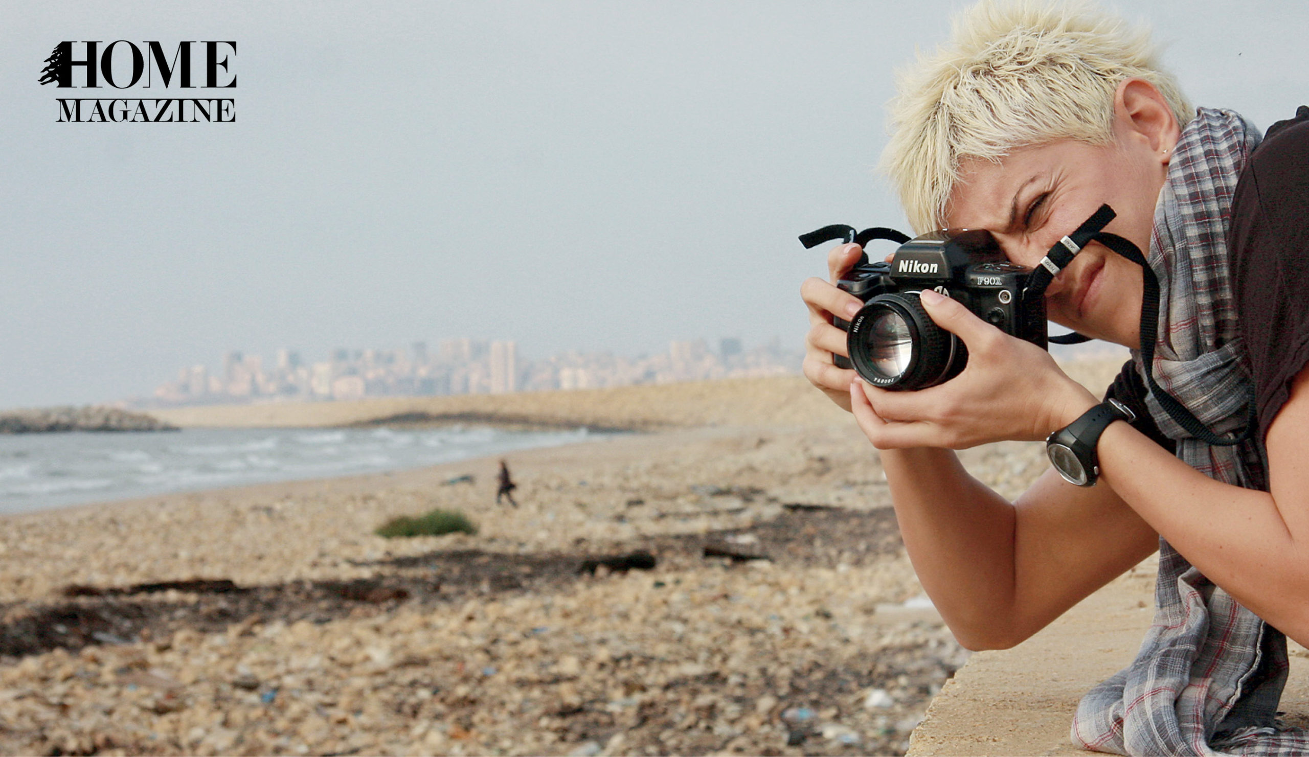 Woman with blond spike hair and scarf taking a picture with a black camera