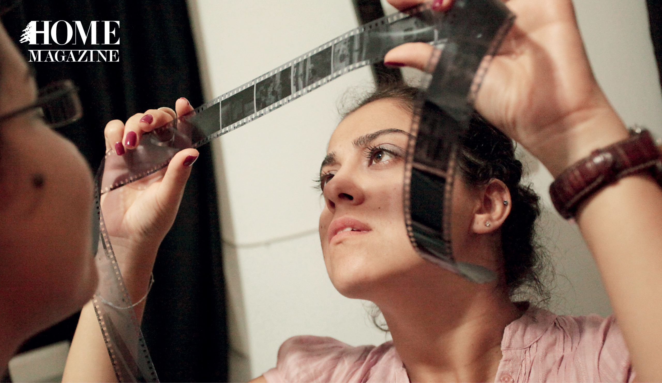 A woman looking through a camera's black film tape