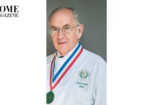 Man of grey hair and eye glasses wearing a medal and a white coat