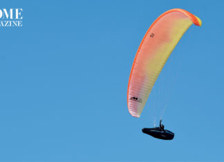 A man flying in the sky with an orange parachute