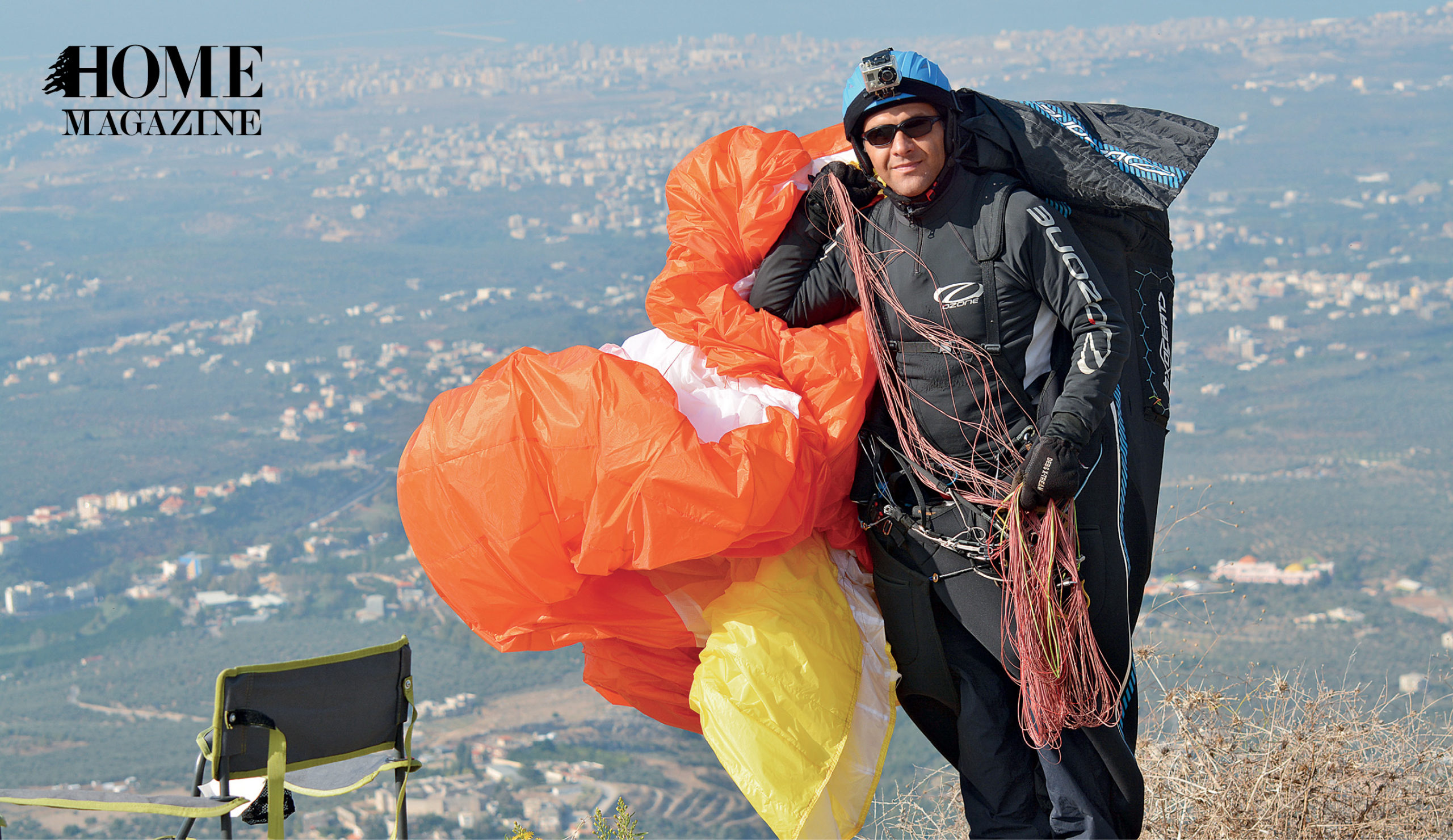 A man in black costume, helmet and sunglasses holding a foiled red and yellow parachute