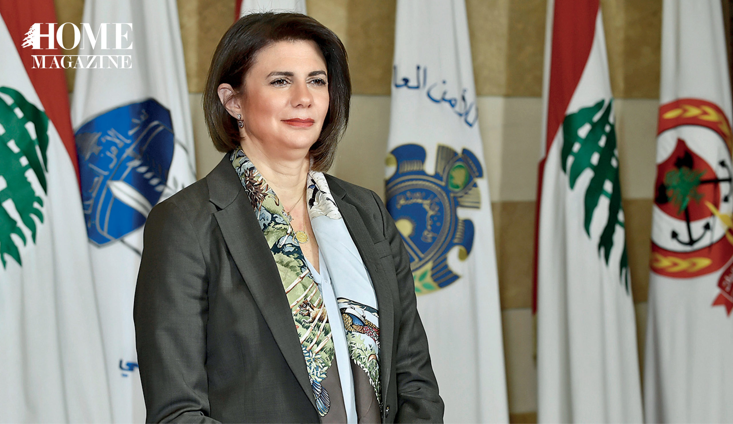 Woman in suit standing in front of flags