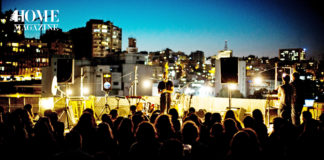 Man performing on stage with crowd and buildings and lights behind him