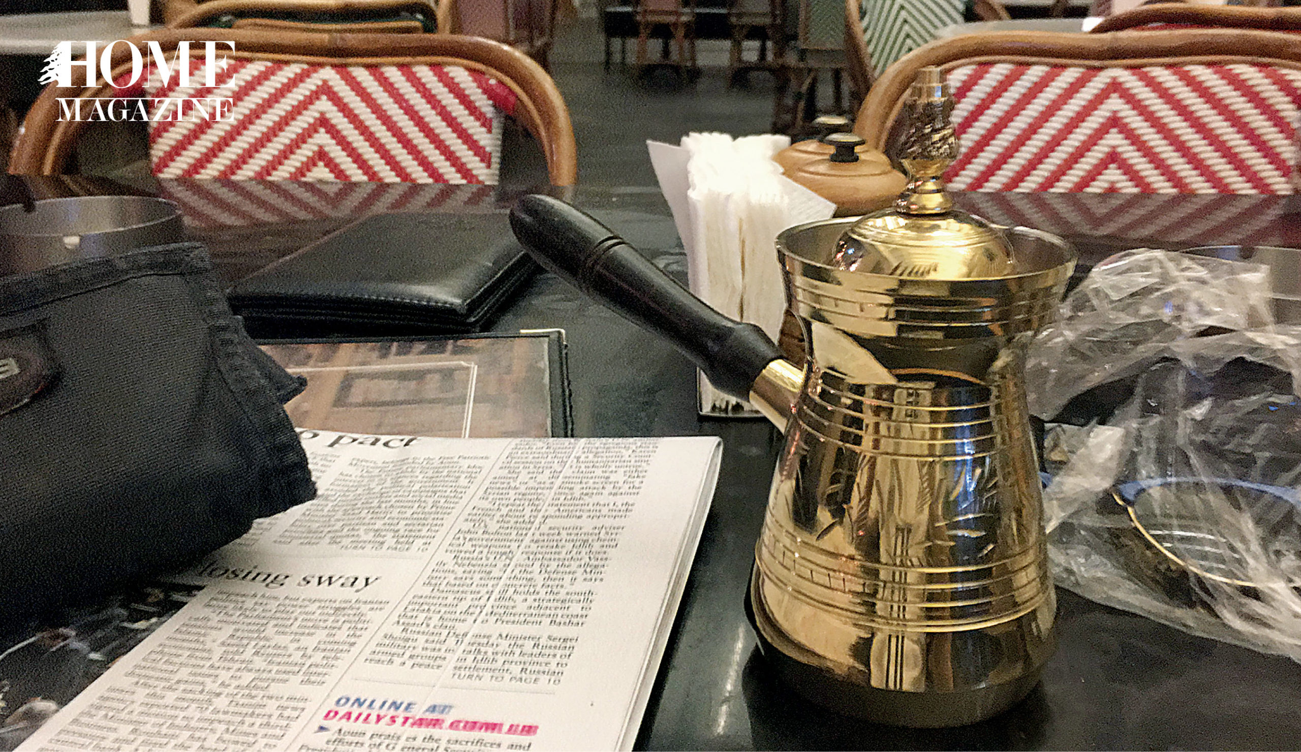 A newspaper, napkins and a coffee boiler on a table