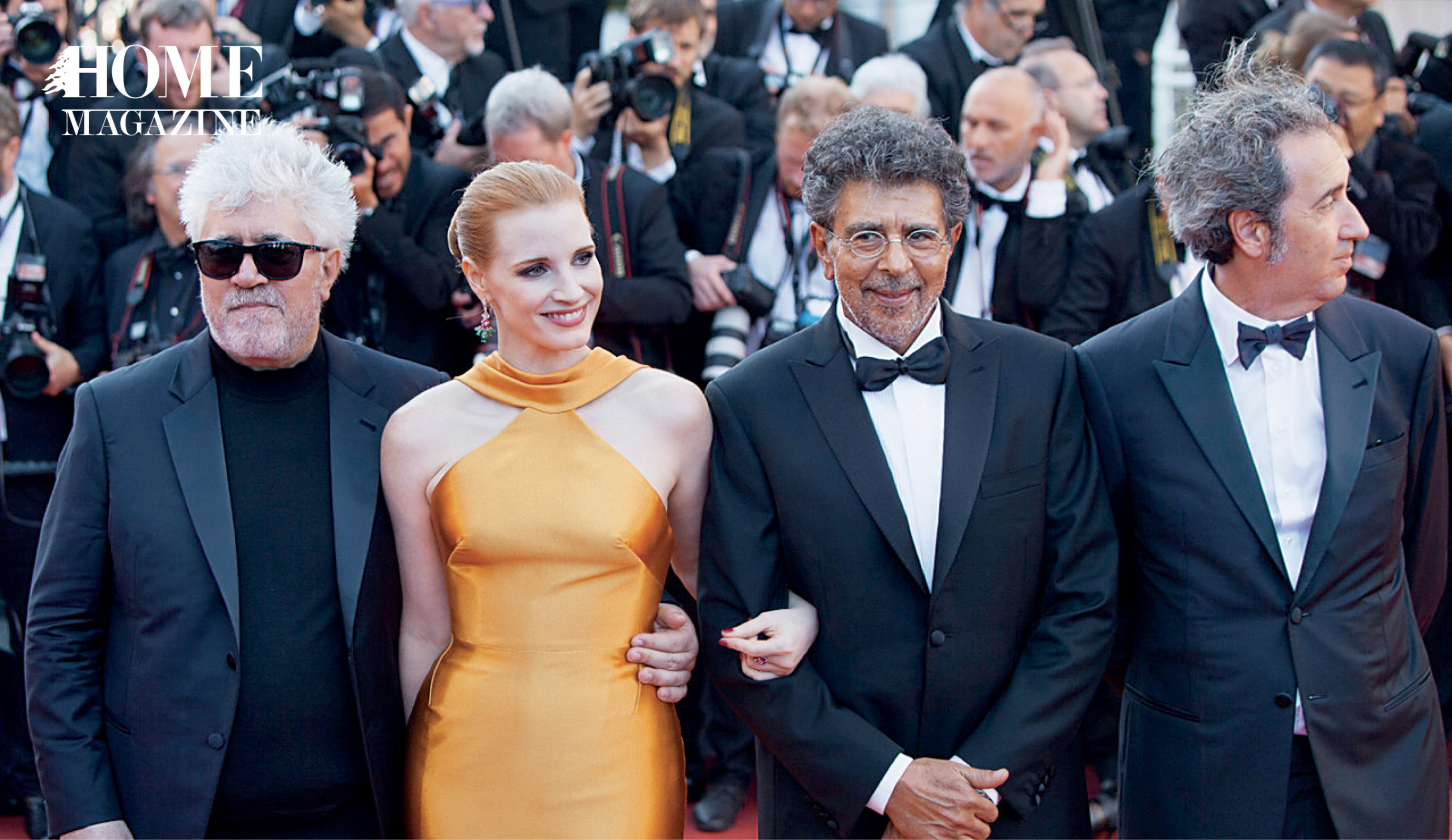 Three men in suits and a lady in an orange dress