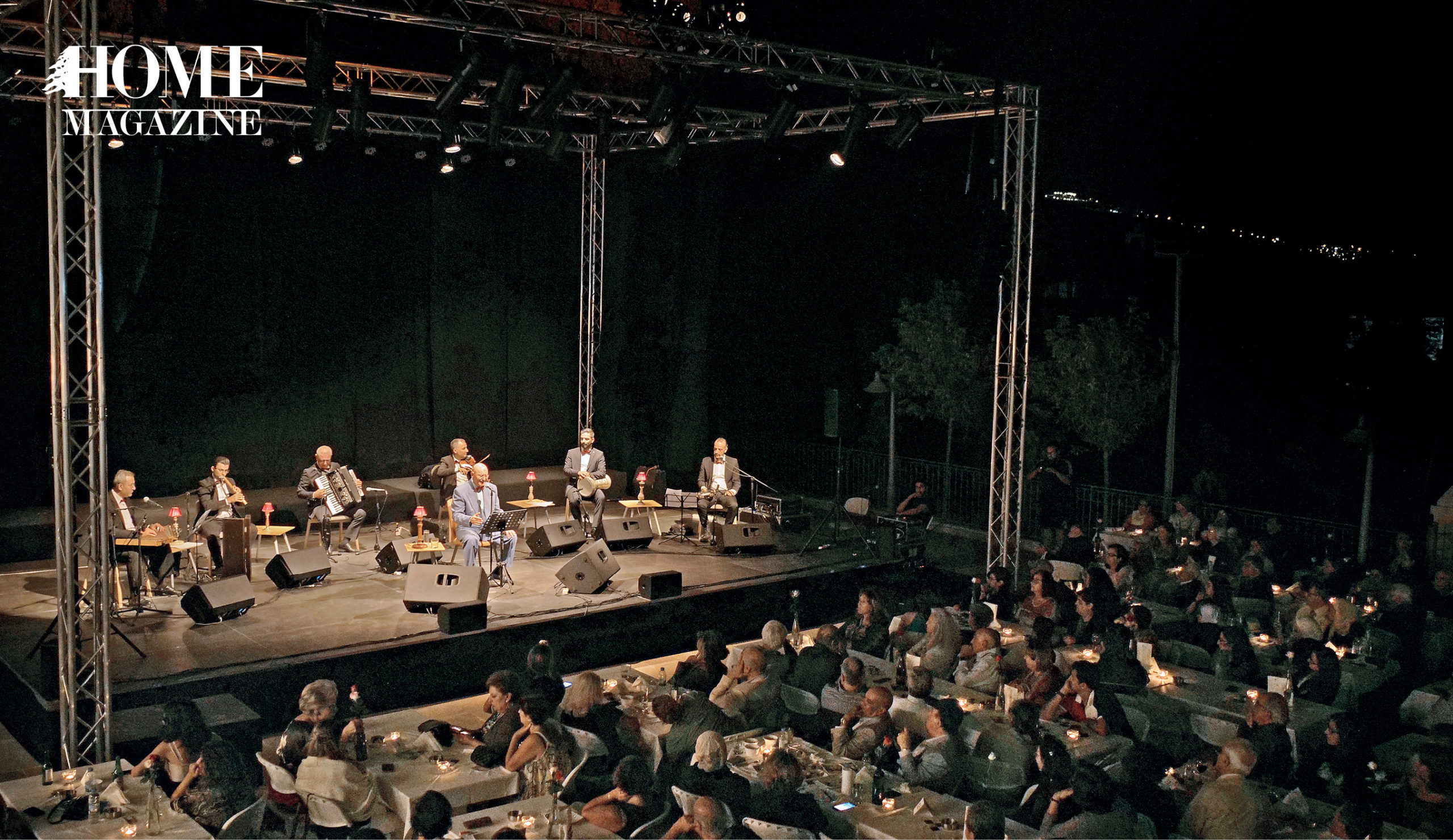 Band performing on stage at night with seated crowd