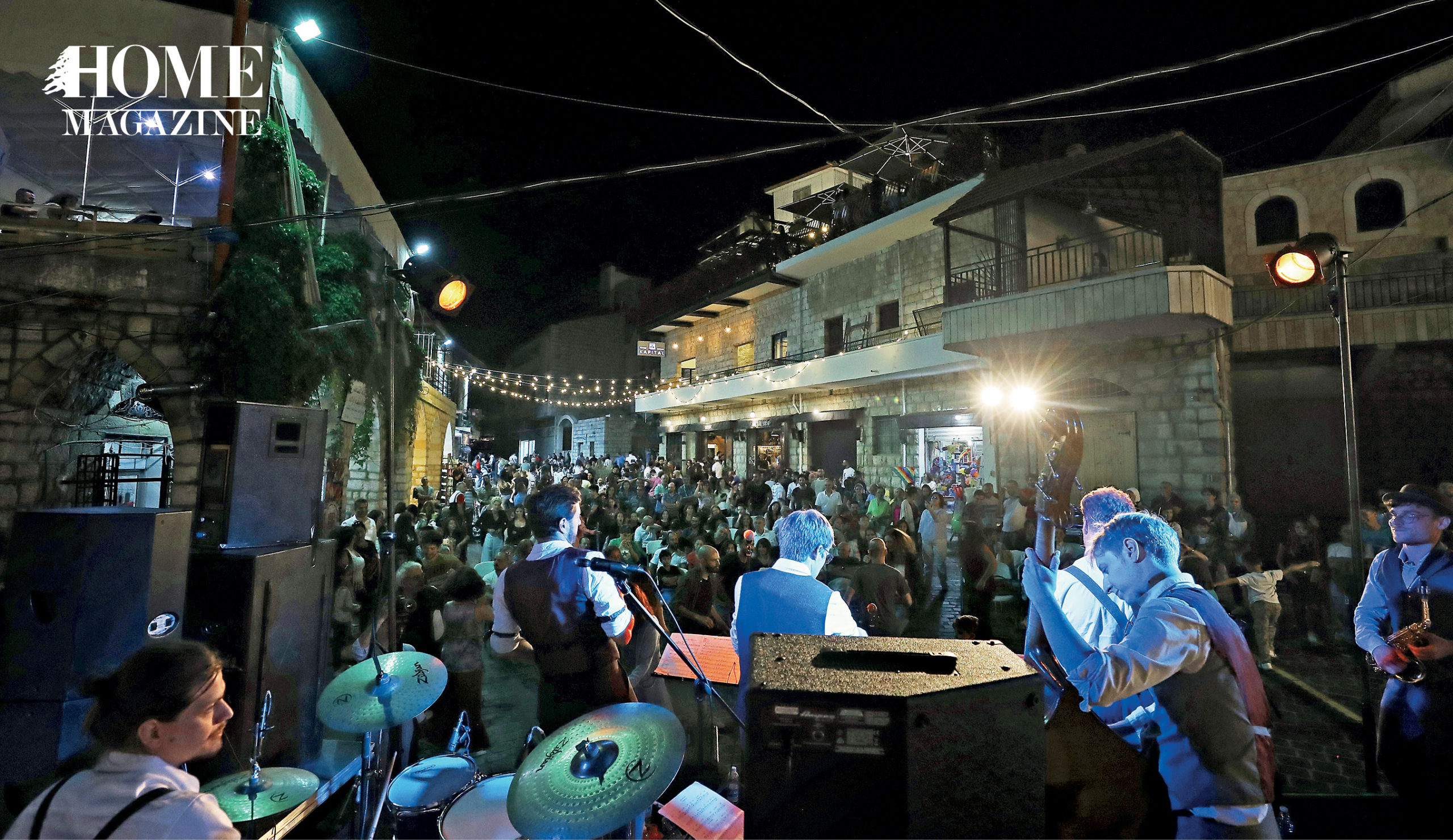 Band performing with crowd amidst buildings and lighting