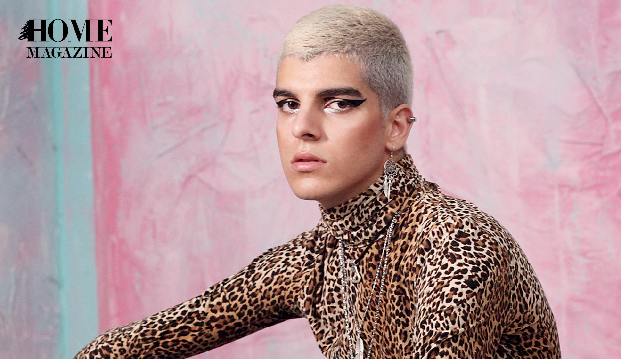 A man with blond hair and make up wearing a tiger printed shirt