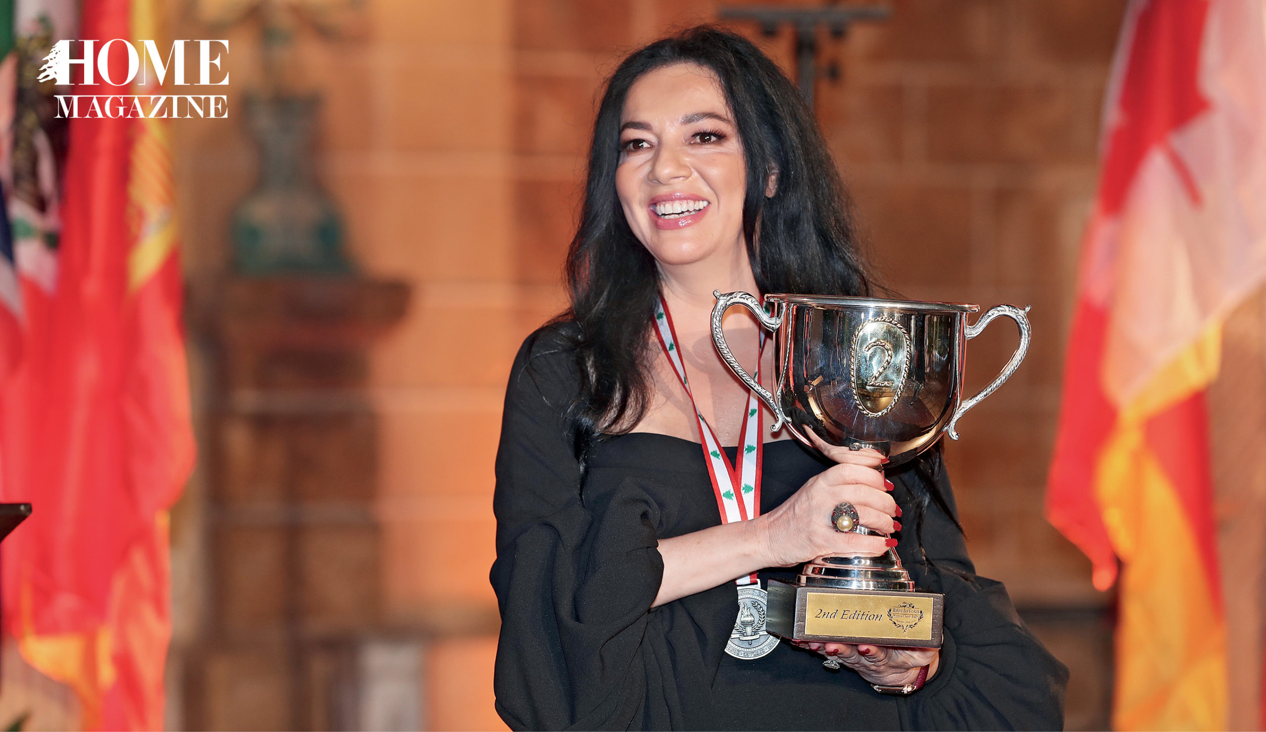 A woman with black hair and in a black dress holding a trophy and a medal around her neck
