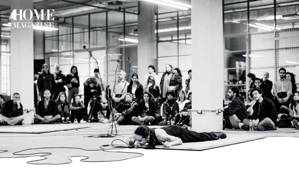 Black and white picture of woman lying on mat floor with microphone in room and crowd behind her